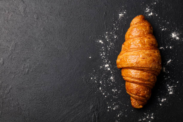 Fresh croissant on a black slate background. Top view. Copy space - foto stock