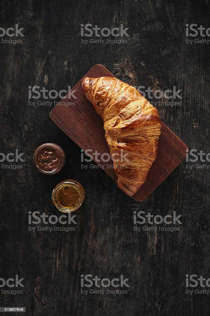 Fresh croissant with chocolate and honey for breakfast stock photo