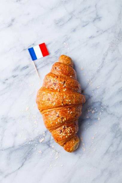 croissant fresco con bandera francesa en el fondo de la mesa de mármol. vista superior. copia espacio. - comida francesa fotografías e imágenes de stock