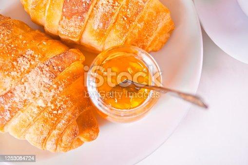 Fresh croissants buns, oranges, orange jam Breakfast concept. Top view