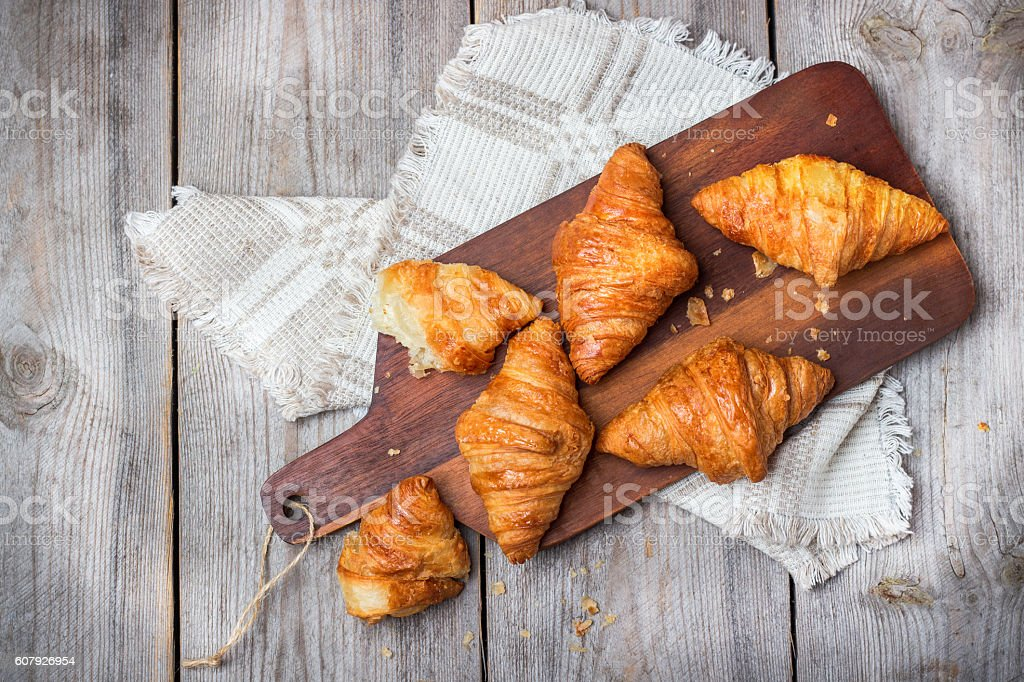 Fresh croissants for breakfast on cutting board rustic table stock photo