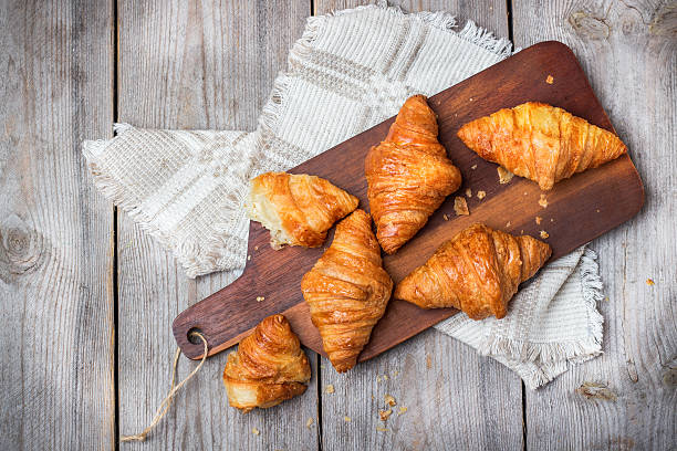 Fresh croissants for breakfast on cutting board rustic table - foto stock