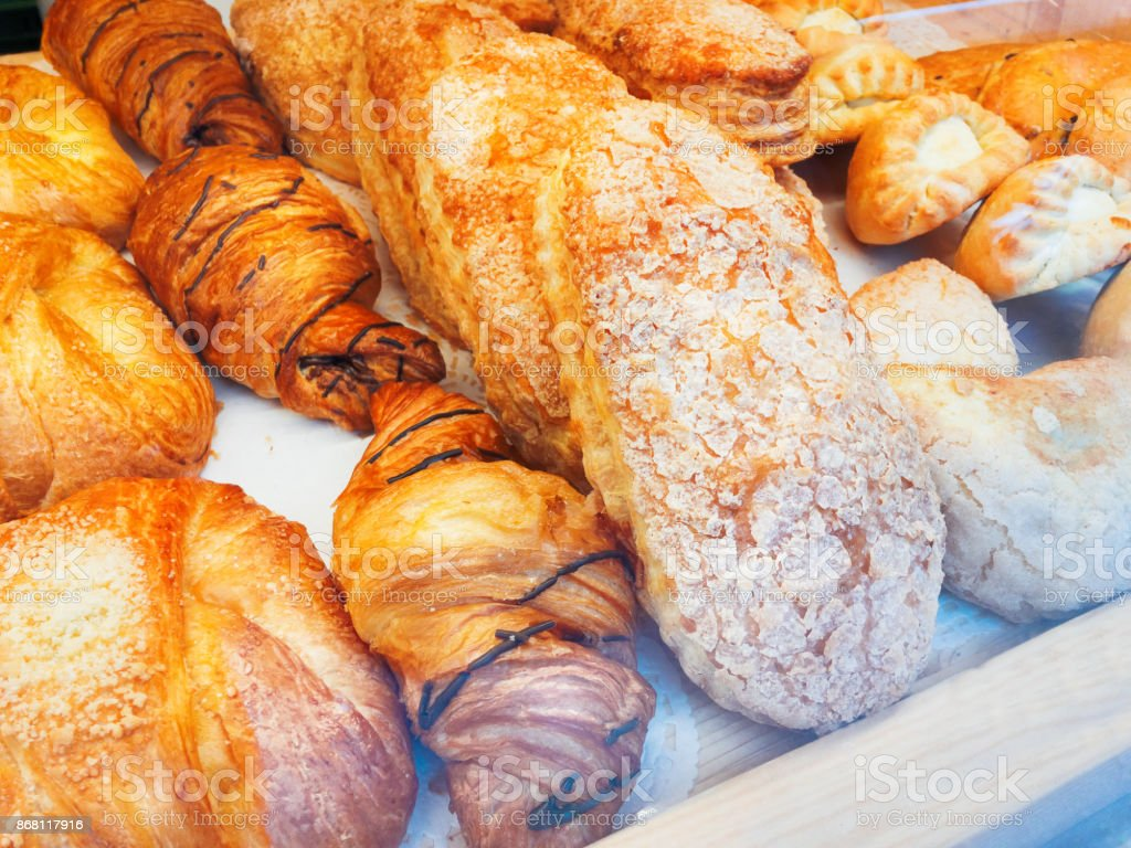 Fresh croissants lie in the shop window. Baked rolls in storefront. Tasty and fresh pastry. stock photo