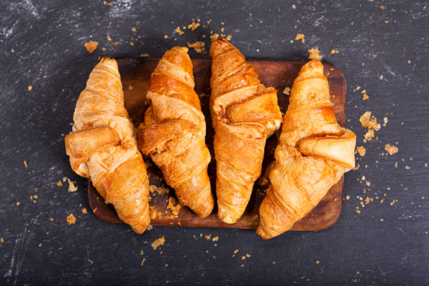 fresh croissants on a wooden board - foto stock