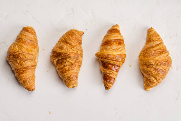 Fresh Croissants on concrete background, flat lay stock photo