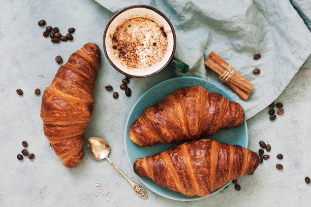 Fresh croissants, together with espresso coffee on a blue background. The view from the top. - foto stock