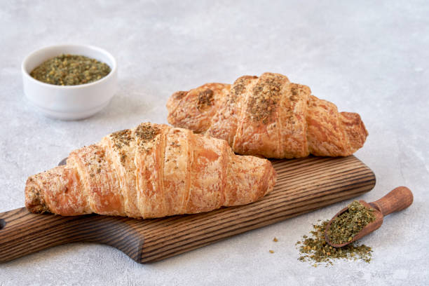 Fresh croissants with zaatar on wooden board Baked Pastry Item, Croissant, Breakfast zaatar spice stock pictures, royalty-free photos & images