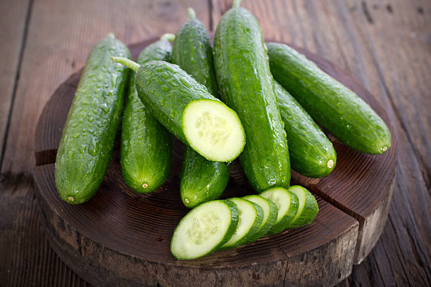 fresh cucumber on the wooden table - cucumber stock photos and pictures