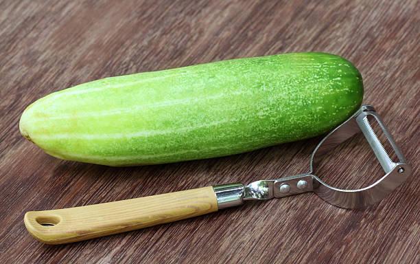 frische gurke mit peeler - peeling zu hause machen stock-fotos und bilder
