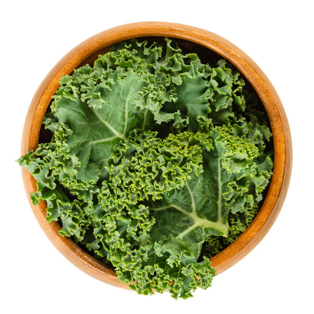 Fresh curly kale leaves in wooden bowl over white stock photo