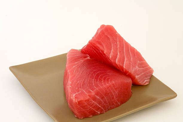 Fresh cut Ahi on a square tan plate ready to cook stock photo