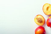 Fresh cut and whole nectarines on a white background. Copy space.