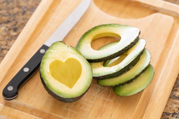 Frisch geschnittene Avocado mit herzförmigen Boxenbereich auf Holzbrett – Foto