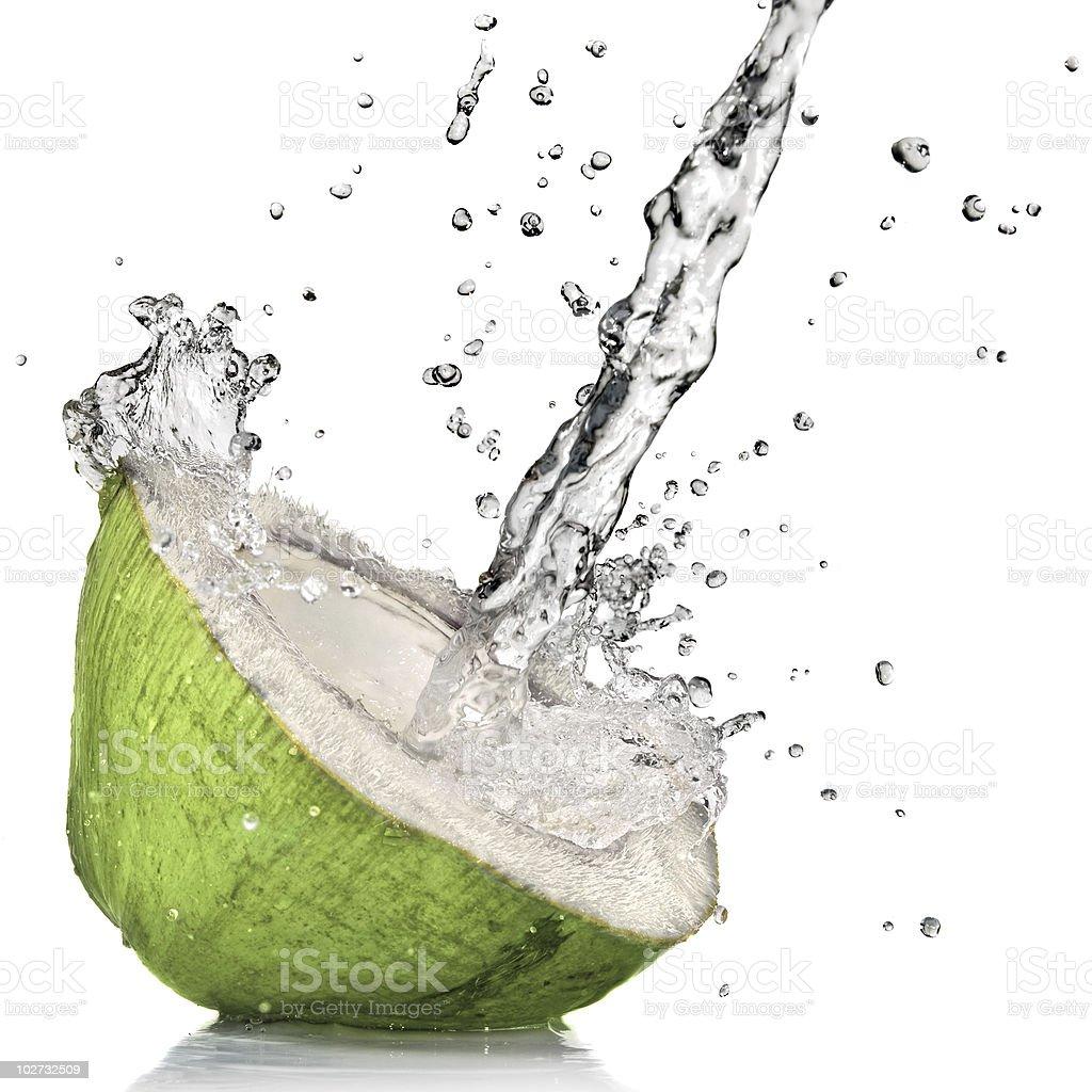 Corte de coco verde fresco com splash em água branca - foto de acervo