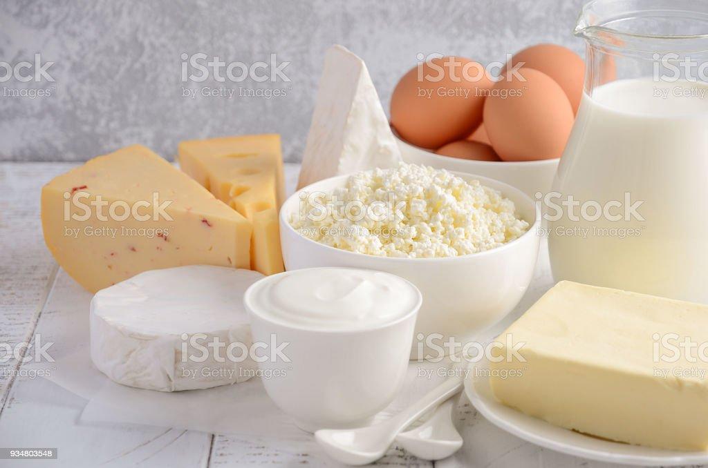 신선한 낙농 제품입니다. 우유, 치즈, 브리, 카망베르, 버터, 요구르트, 코 티 지 치즈와 나무 테이블에 알. - 로열티 프리 개체 그룹 스톡 사진