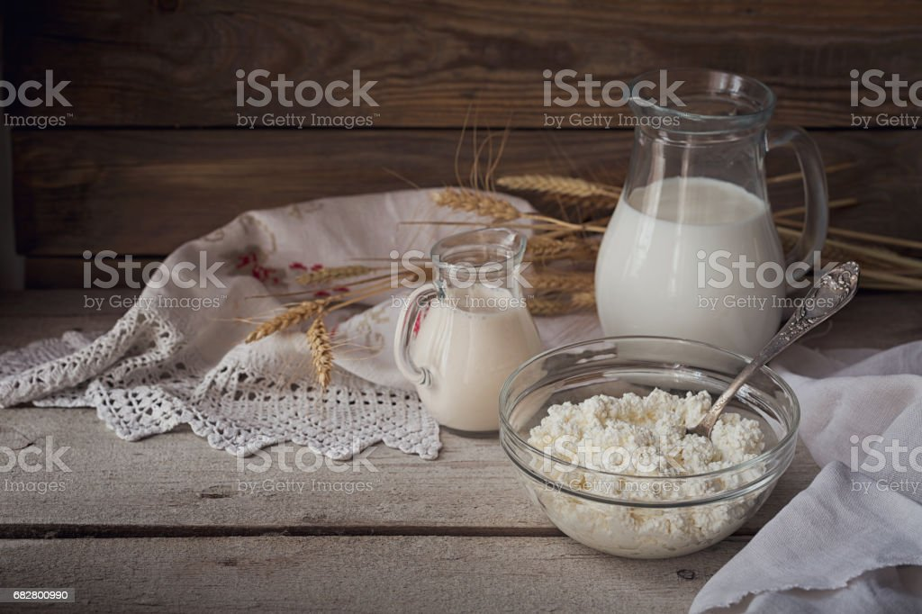 Fresh dairy products: milk, cottage cheese, sour cream and wheat on rustic wooden background. Lizenzfreies stock-foto
