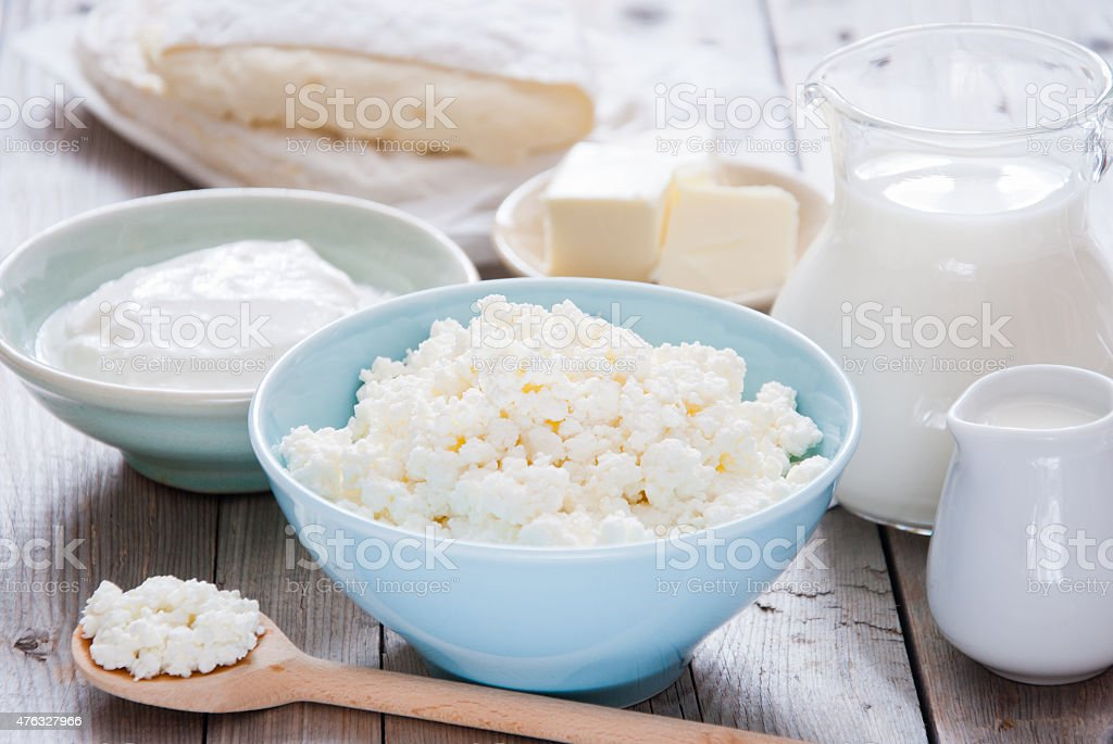 Organic Farming Cottage cheese in a blue bowl, sour cream, butter,...