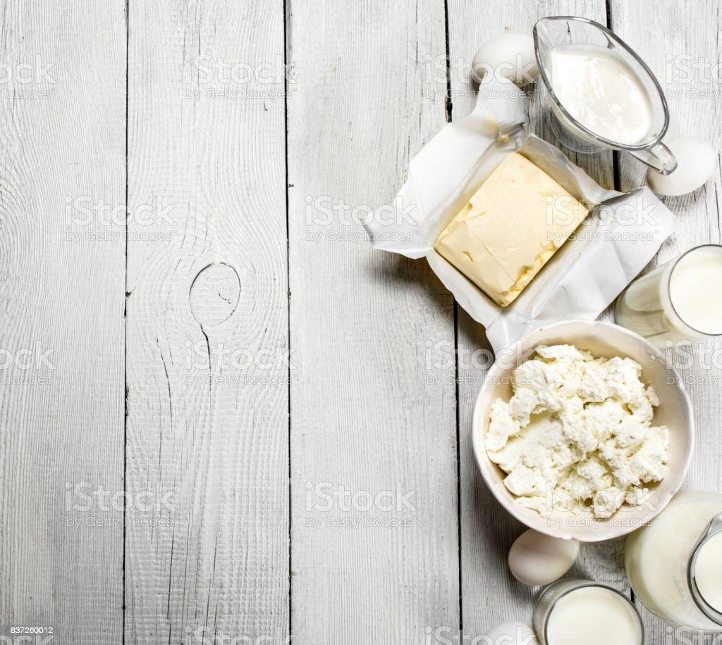 Fresh dairy products on white wooden background.