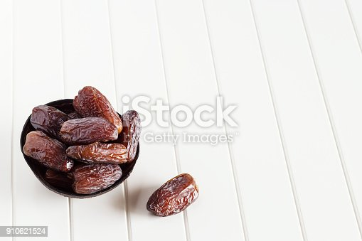 istock Fresh dates Medjool in wooden coconut bowl. White background. Selective focus. Copy space. 910621524