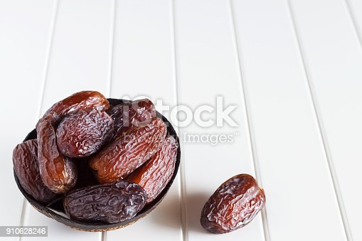istock Fresh dates Medjool in wooden coconut bowl. White background. Selective focus. Copy space. 910628246