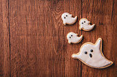 istock Fresh delicious homemade decorated halloween cookies sweets on dark wooden background, concept of halloween party, copy space(text space), top view, blank for text. 1051739898