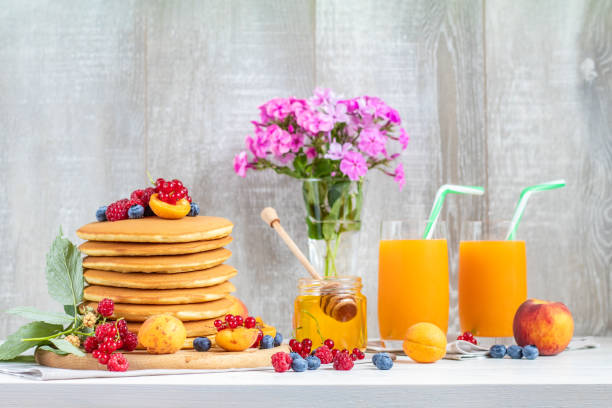 Fresh delicious pancakes with summer berries on light surface stock photo