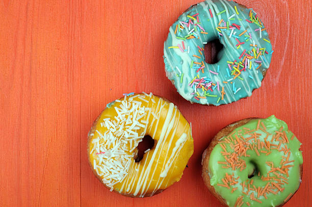 Fresh  donuts in soft colorful glaze on  orange  wooden background stock photo
