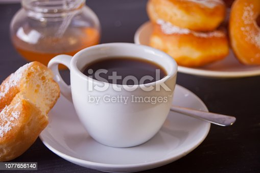 Fresh donuts with cup of coffee on the wooden dark table