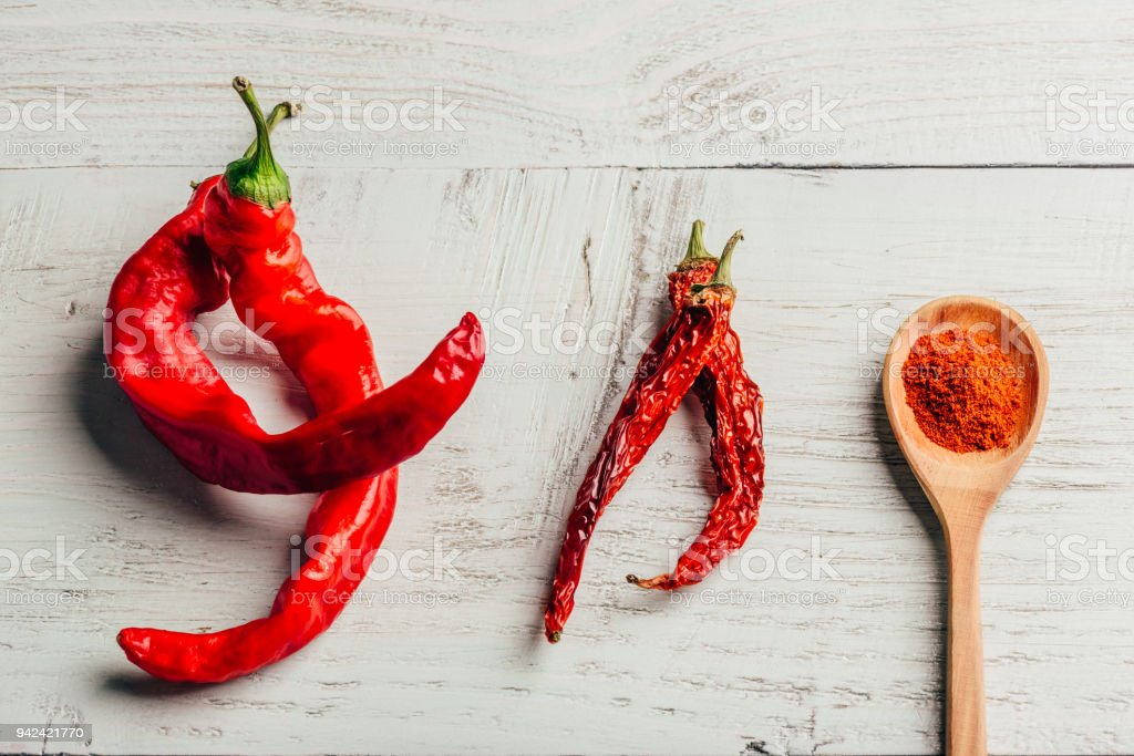 Fresh, dried and ground red chili pepper stock photo