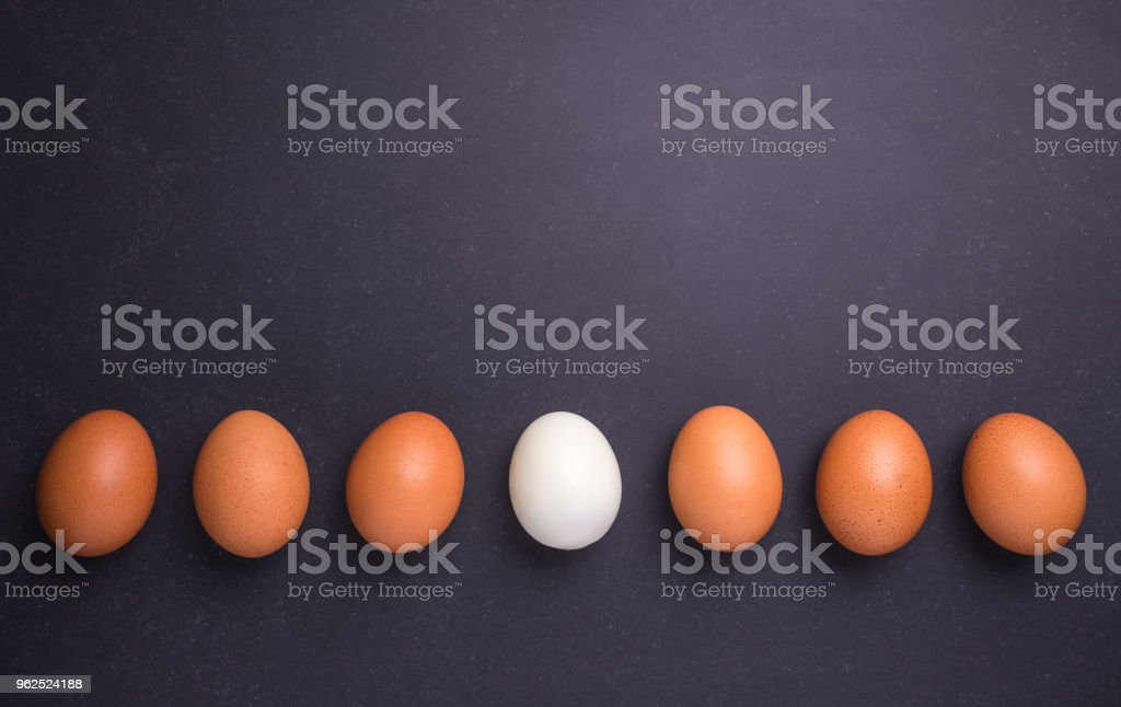 Fresh egg and boiled egg without shell. Top view on black stone - Royalty-free Above Stock Photo