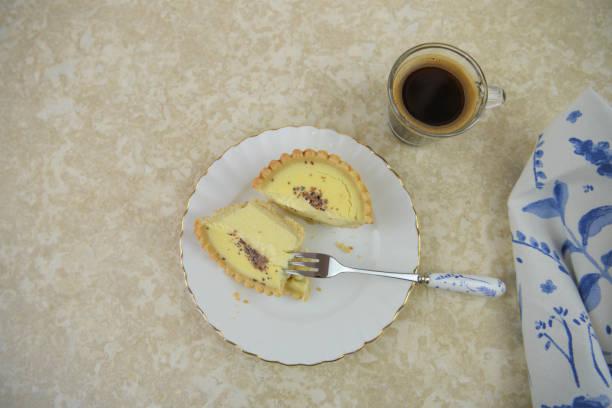 frisches ei puddingtörtchen mit heißem kaffee auf einem marmortisch - portugiesische desserts stock-fotos und bilder