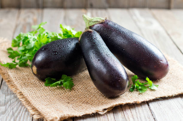 fresh eggplant on wooden background - group of people стоковые фото и изображения