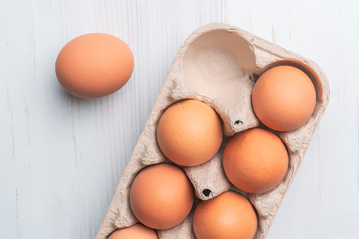 istock fresh eggs in paper tray on white surface b 1085962980