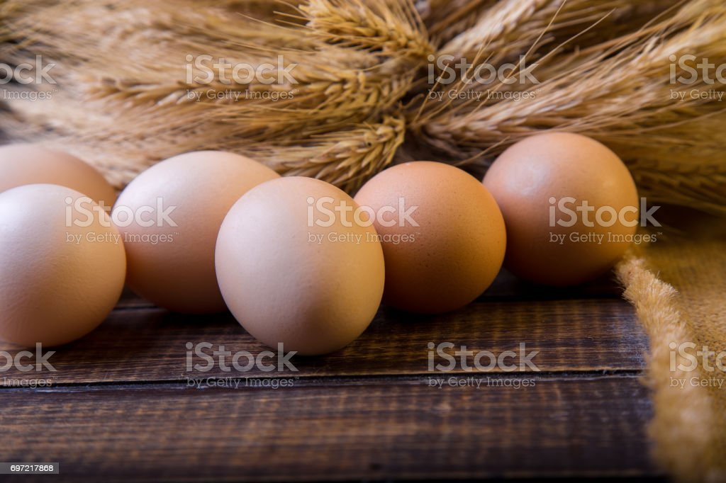Fresh eggs near wheat  on wooden background.  Rustic. stock photo