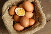 Fresh eggs and boiled egg on a wooden rustic background.