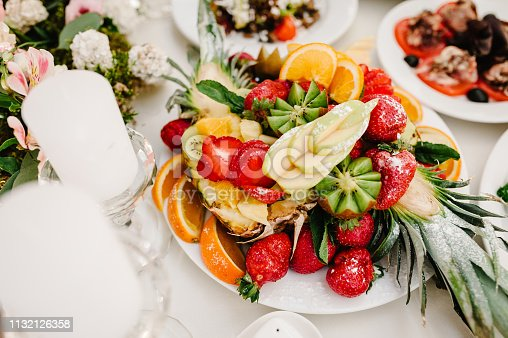 Fresh, exotic, organic fruits, light snacks in a plate on a buffet table. Assorted mini delicacies and snacks, restaurant food at event. Decorated delicious table for a party goodies.