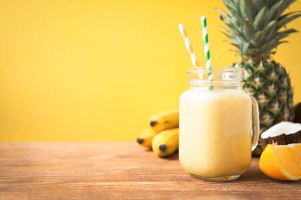 taze egzotik meyve ve sarı zemin üzerine hindistan cevizi sütü ile güler yüzlü. - hindistan cevizi tropik meyve stok fotoğraflar ve resimler