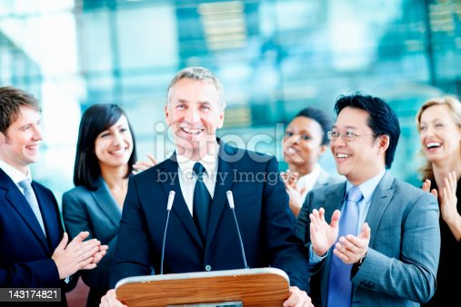 Smiling diverse political team clapping for their representative as he stands at the podium