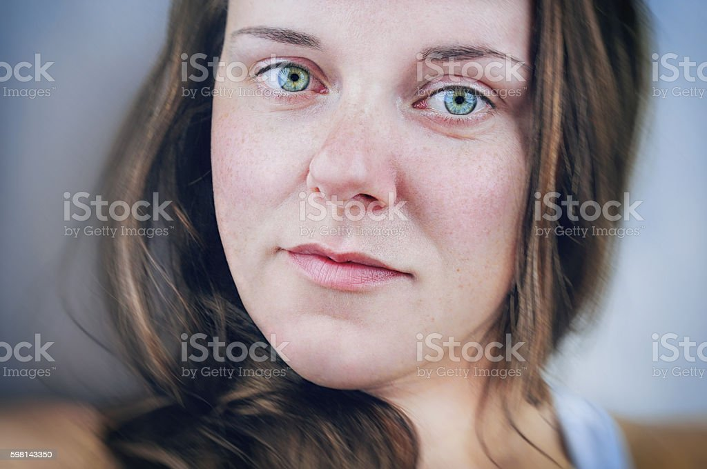 Fresh faced make-up free young woman with bright green eyes. stock photo