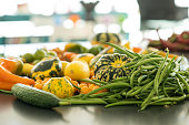 An assortment of farmer's market tomatoes, squash, and green beens arranged on a black kitchen counter top.