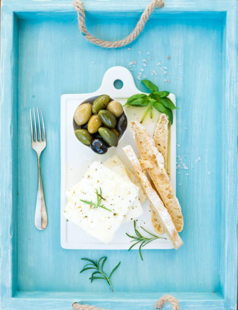 fresh feta cheese with olives, basil, rosemary and bread slices on white ceramic serving board over bright turquoise blue painted wooden background - tablett holz stock-fotos und bilder