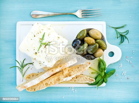 istock Fresh feta cheese with olives, basil, rosemary and bread slices 866898664