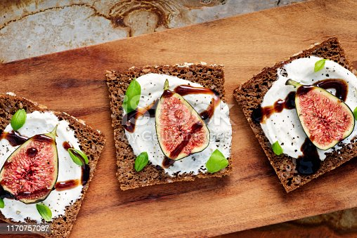 Overhead, close-up  view of fresh figs with ricotta cheese, fresh basil leaves on rye bread with a drizzle of balsamic vinegar. Colour, horizontal with some copy space.