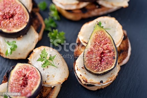 Overhead, close-up  view of a dish of fresh figs with  melted goats cheese on top of toasted french bread. Colour, horizontal with some copy space. Photographed just as they come out of the grill with the cheese melting.
