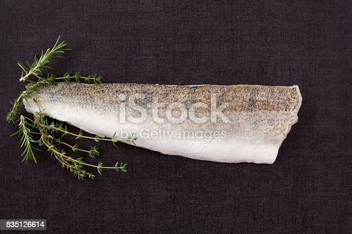 Fresh Fillet fish slice with thyme and rosemary on black surface from above. Culinary seafood eating.