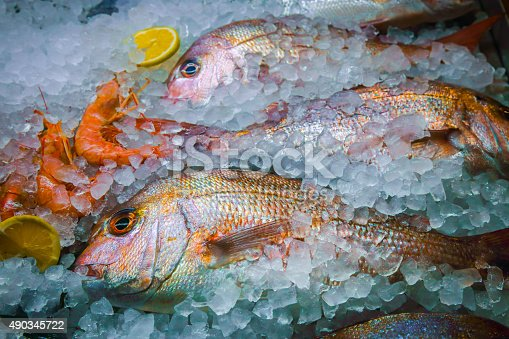 Fresh fish, shrimps and lemon on ice,