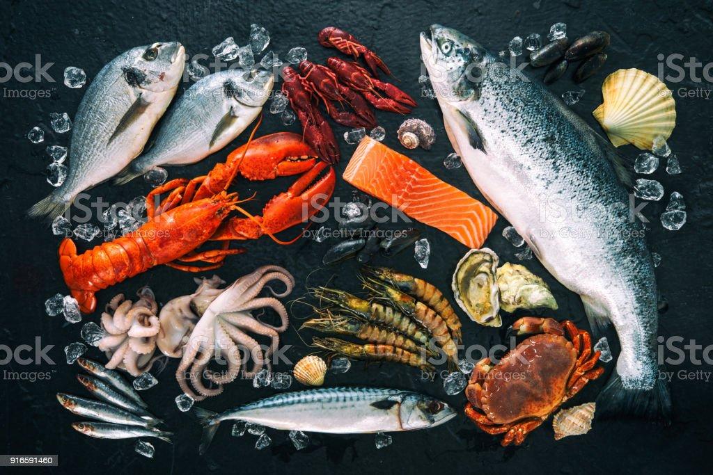 Arranjo de peixe e marisco fresco na pedra preta - foto de acervo