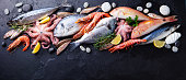 Fresh fish and seafood assortment on black slate background. Copy space. Top view.