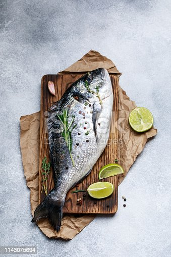 Fresh fish dorado. Raw dorado fish and ingredient for cooking. Fresh fish gilt-head bream dorade with salt, herbs and pepper.