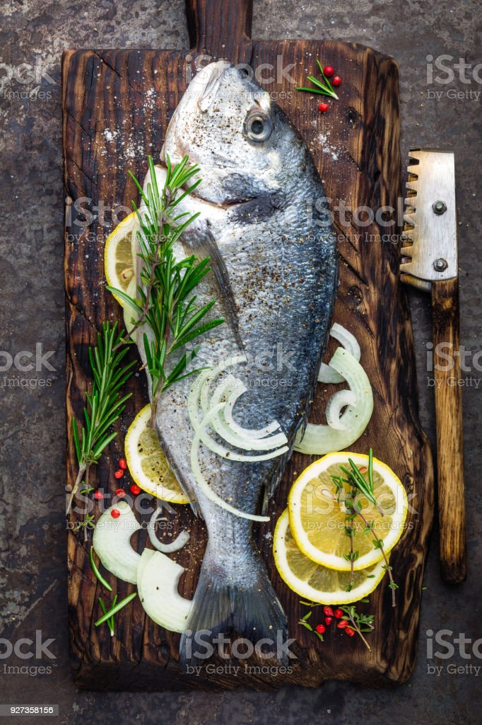 Fresh fish dorado with ingredients for cooking on wooden board. Raw sea bream or dorada fish on dark vintage metal background. Dietary food. Top view Fresh fish dorado with ingredients for cooking on wooden board. Raw sea bream or dorada fish on dark vintage metal background. Dietary food. Top view Above Stock Photo